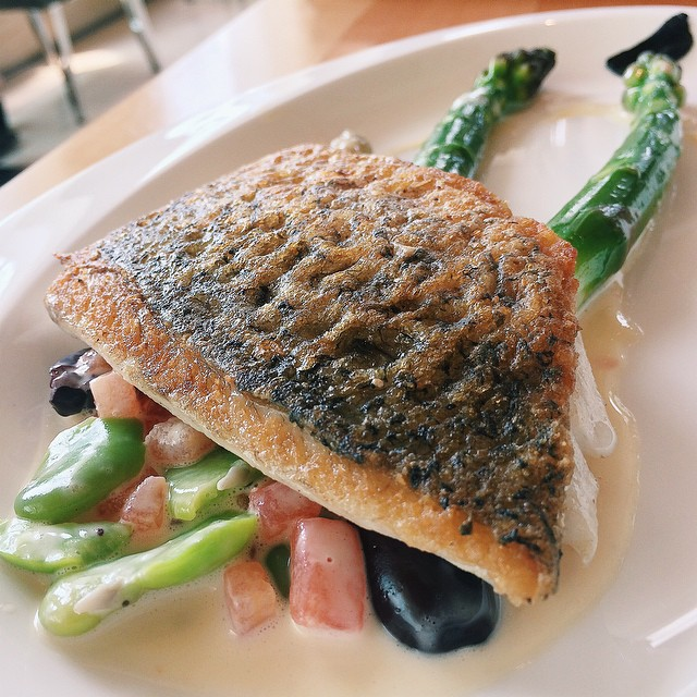 """Seared sea bass fillet with asparagus, tomatoes and olives from Chef Andrew Turner's """"Cooking with Friends"""" guest chef programme menu, which is only available 13 - 16 May."""