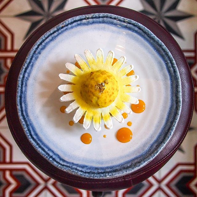 """Hope your day is as bright as this gorgeous """"Sunny"""" sunflower plated dessert 🌻 the coconut biscuit base and almond sponge body held so many things within and on top: Chamomile Honey Parfait, Ginger Lime Foam, Pure Peppermint Tea Infused Peach, Lemongrass Apricot Coulis, and Chamomile Espuma."""