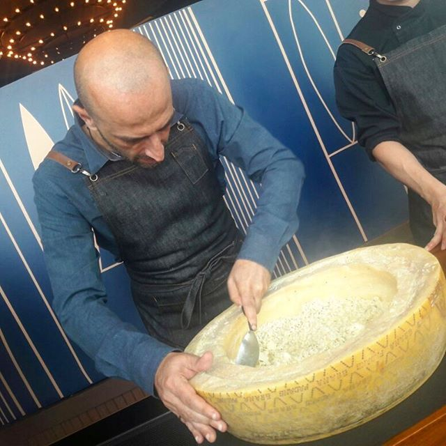 Scooping around the gigantic cheese wheel for our risotto.